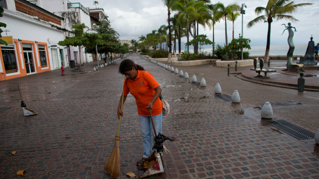 A city cleaner sweeps normal leaves and debris from a seafront walkwa