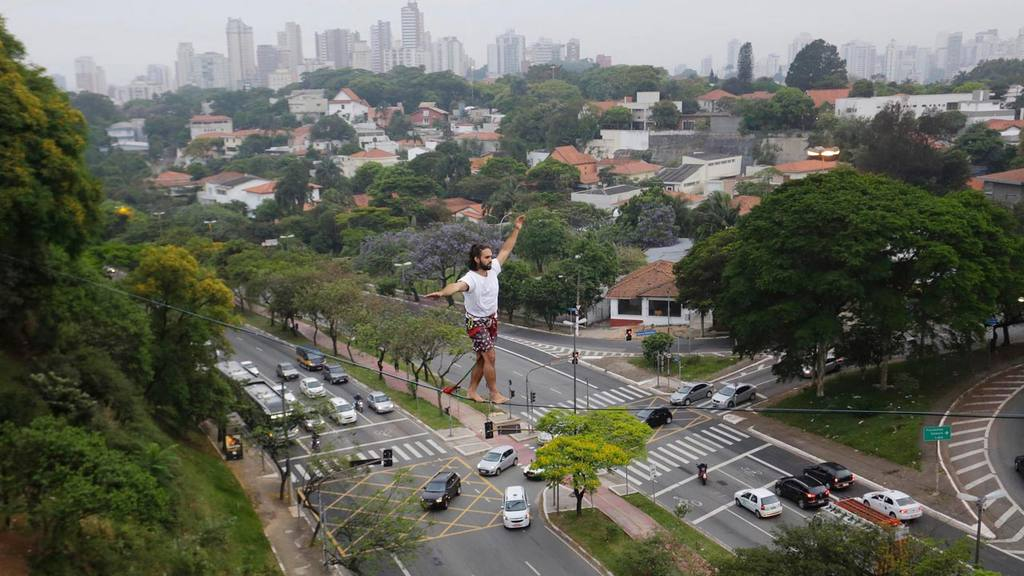 Guilherme Coury, 23, walks on a flat line, anchored between a tree an