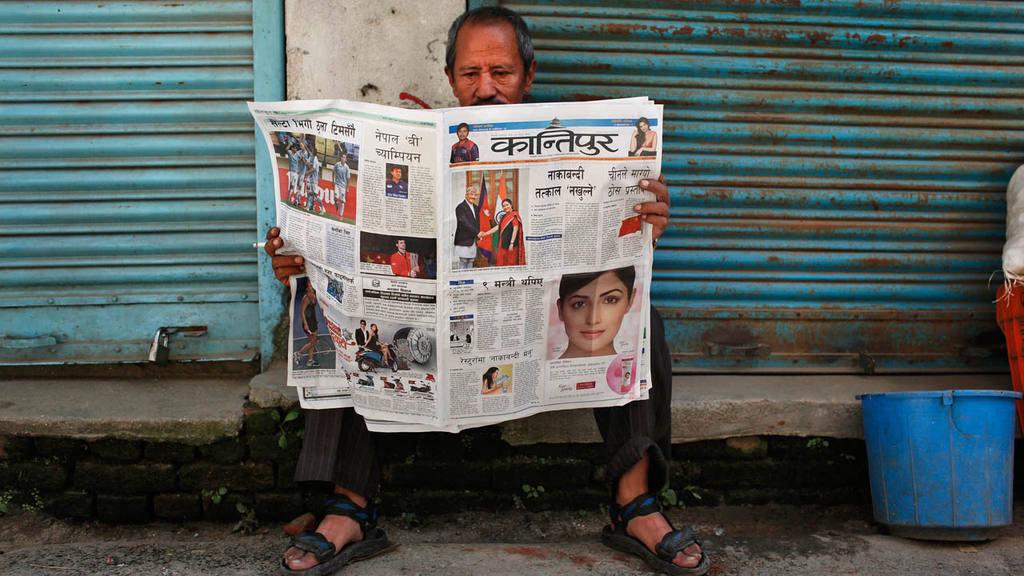 A Nepalese man reads a newspaper in Kathmandu, Nepal, Monday, Oct.