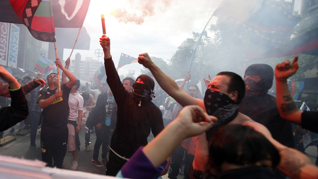 A masked demonstrator lights a flare during a march against the comme