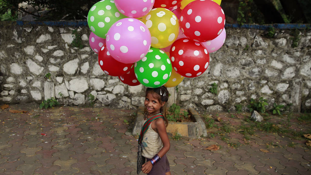 Lali carries balloons to sell on a beach in Mumbai
