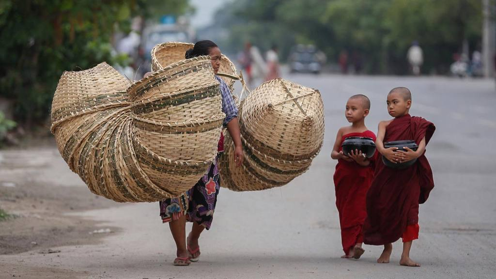Two novice Buddhist monks walk alongside a basket seller to collect a