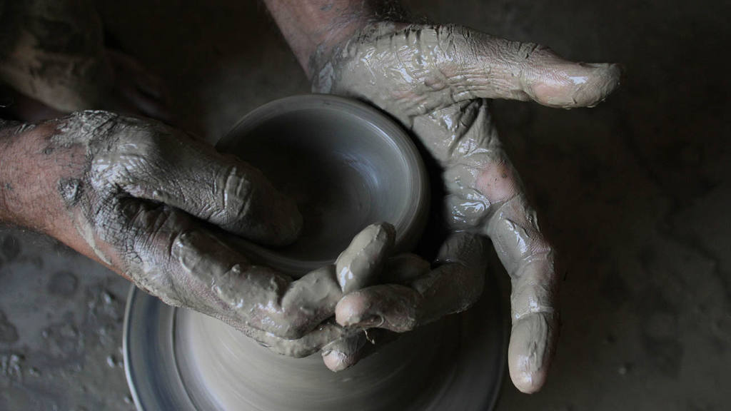 Pakistani potter Afzal Khan uses a pottery wheel to make a pot in Lah