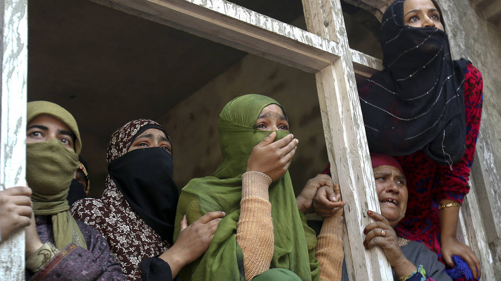 Kashmiri Muslim women watch a funeral procession of suspected rebels