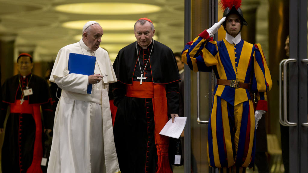 Pope Francis and Cardinal Pietro Parolin are saluted by a Swiss guard