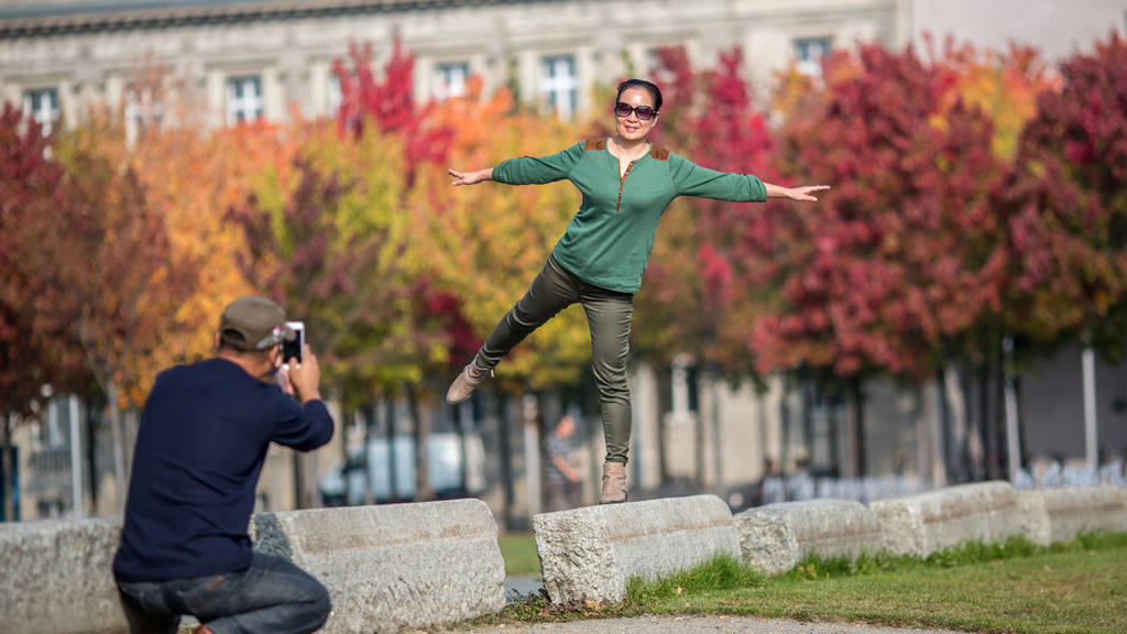 A woman from China is photographed as she jumps in fron of colorful t