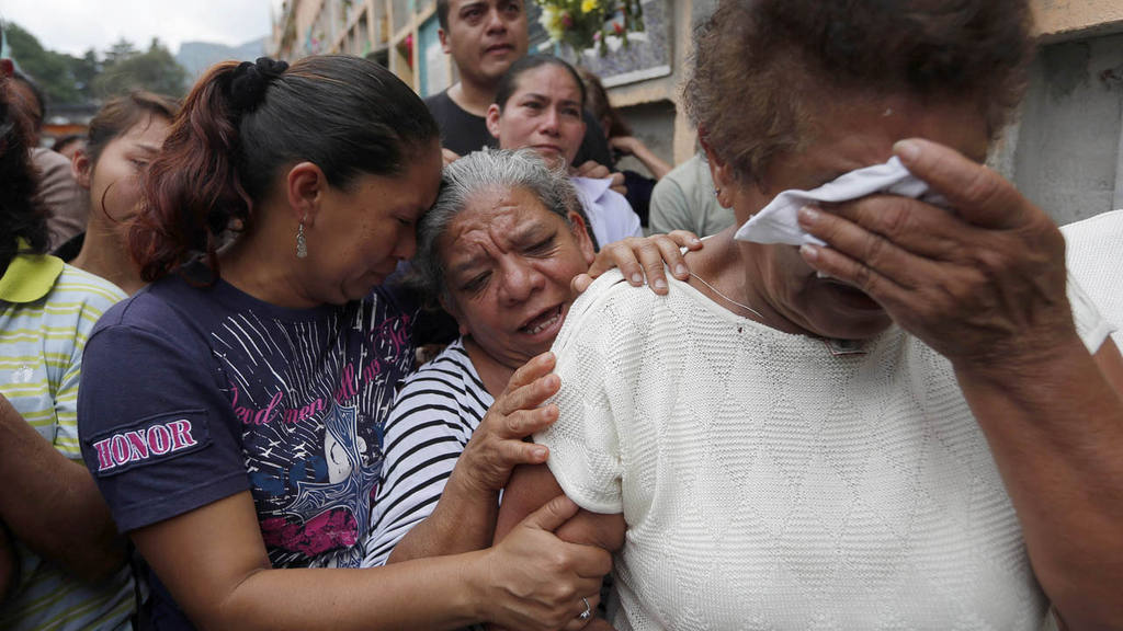 Relatives weep during the burial of Amilcar Estrada and his 10-year-o