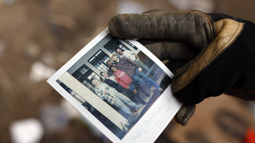A fireman holds a photo of an unidentified family as he searches the