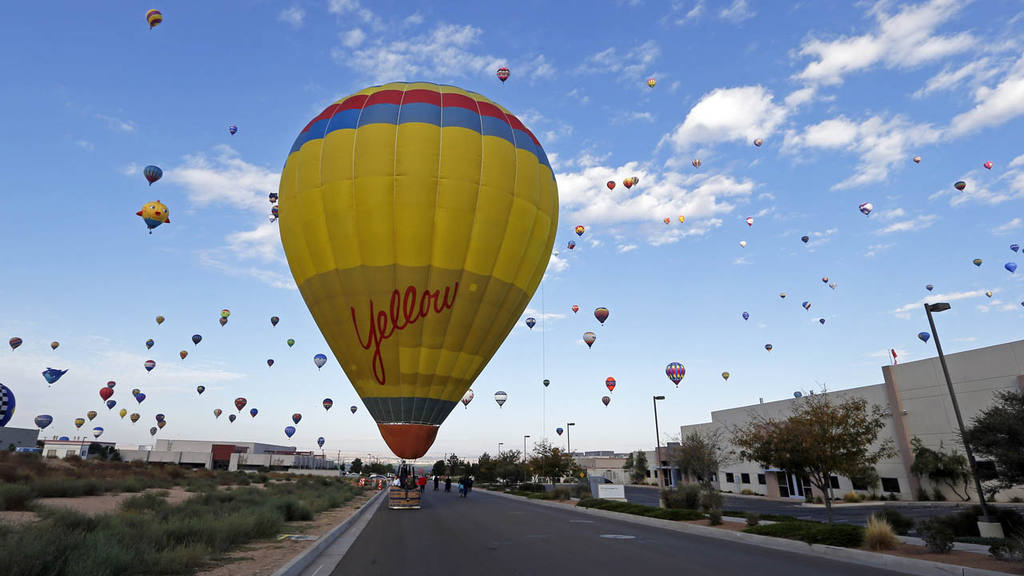 A hot hair ballon lands on a service road as many others fly during t