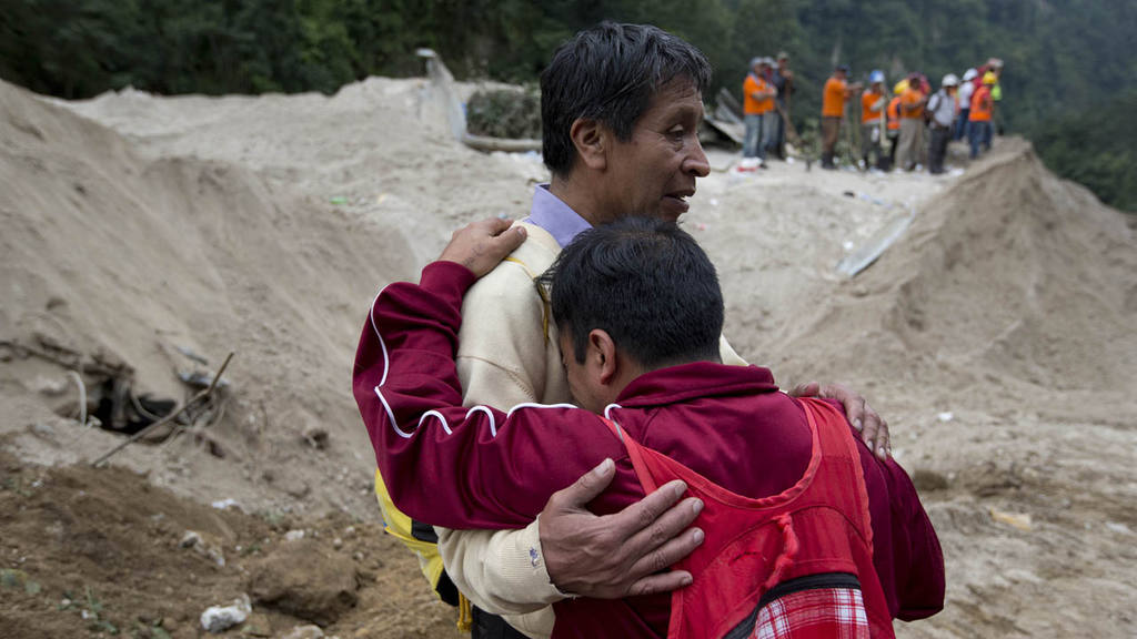 Neighbors comfort each other as rescue workers continue the search at
