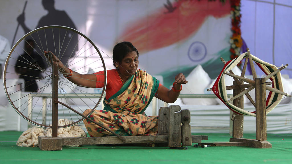 An Indian women makes thread for weaving to mark the birth anniversar