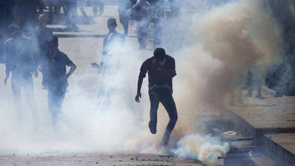 A Kashmiri protester kicks back an exploded tear gas shell fired by I