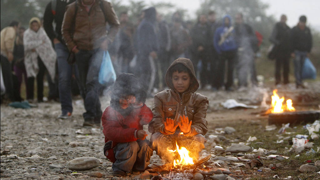 Two boys warm themselves by a fire while other migrants and refugees