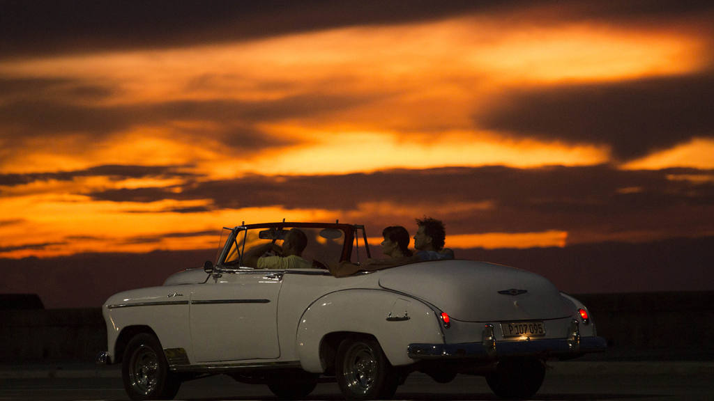 Tourists ride a vintage American convertible during sunset on the Mal