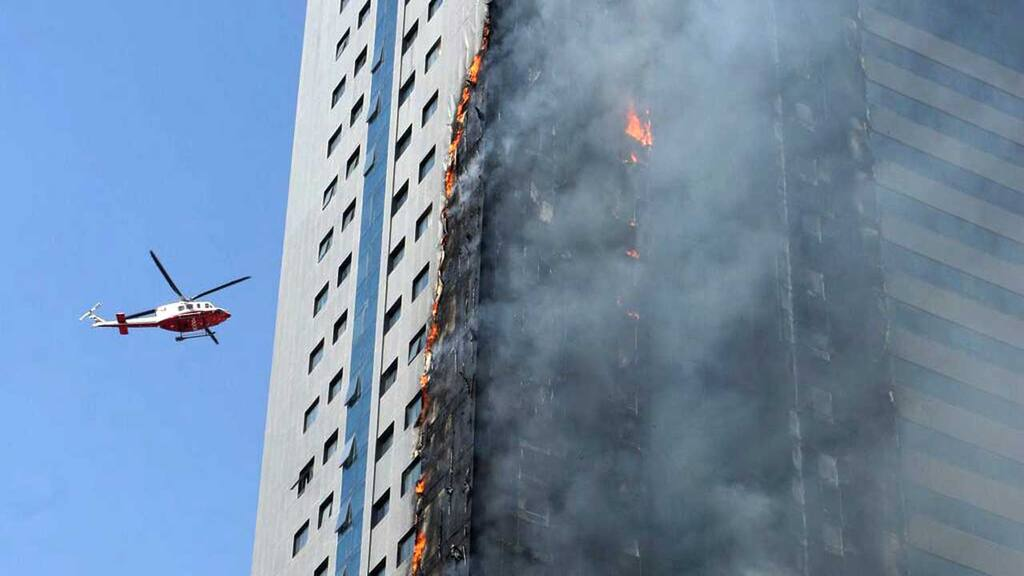A helicopter hovers over a skyscraper which caught fire in Sharjah