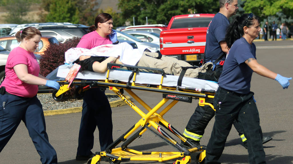Authorities carry a shooting victim away from the scene after a gunma