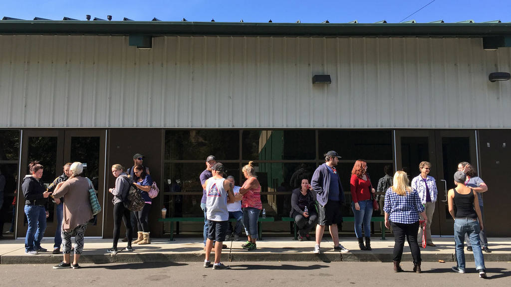 People wait for information at the local fairgrounds after a deadly s