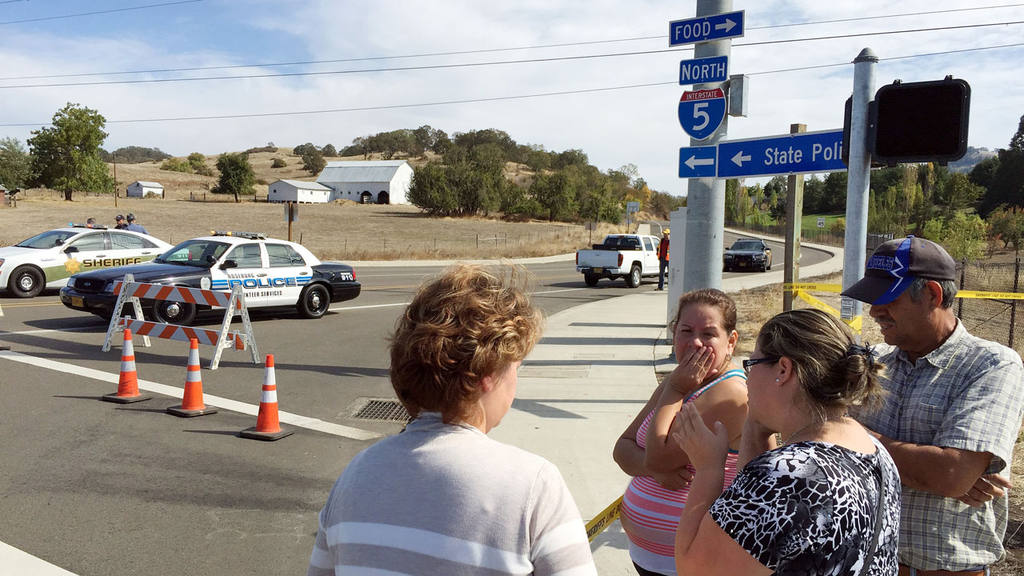 People gather at a road block near the entrance to Umpqua Community C