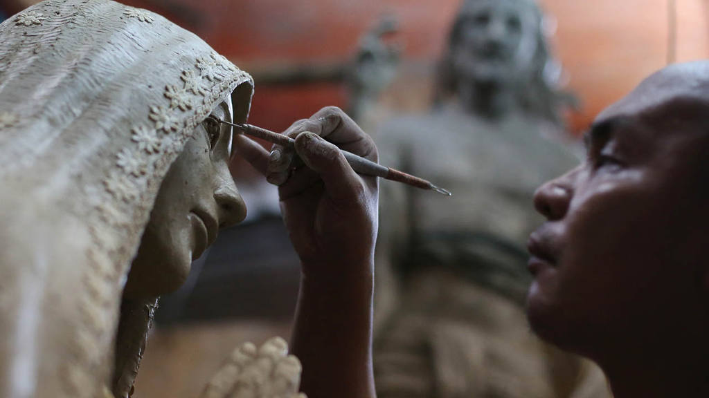 Filipino sculptor Frederic Caedo concentrates as he works on an image