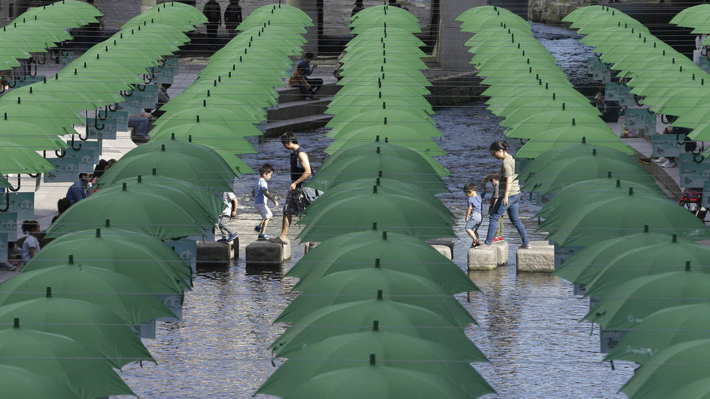 Visitors walk under umbrellas on display over Cheonggye stream during