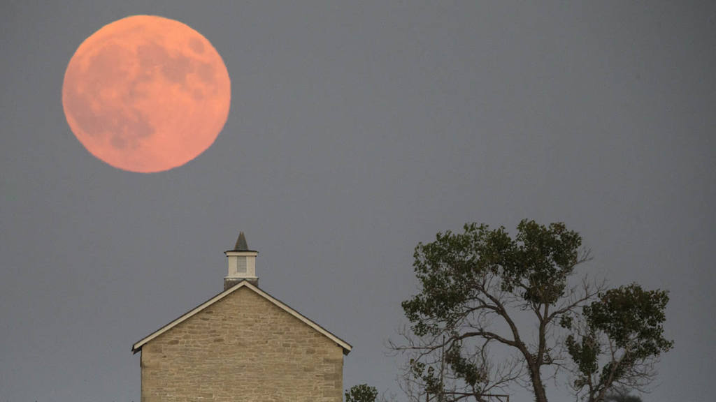 A super moon rises over the Lower Fox Creek School near Strong City