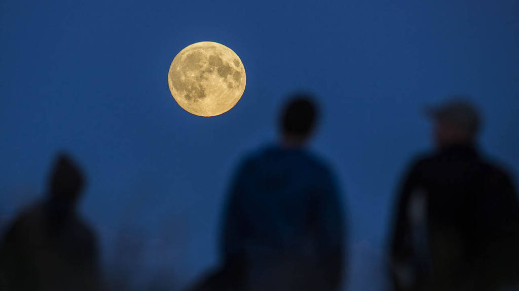 People watch a full moon rising in Berlin, Germany, Sunday, Sept.