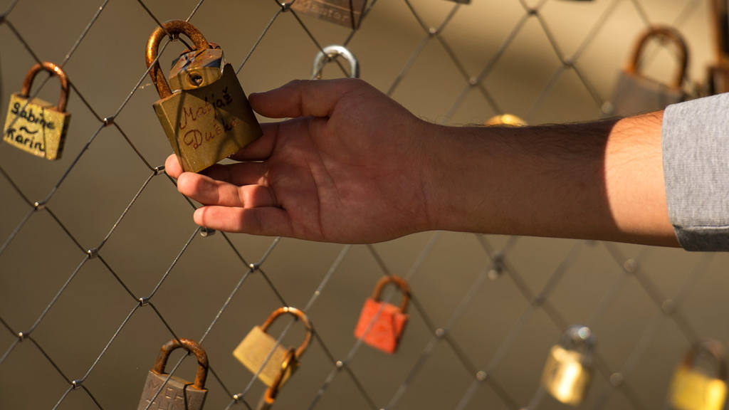A migrant man looks at love locks as he waits for registration on a b