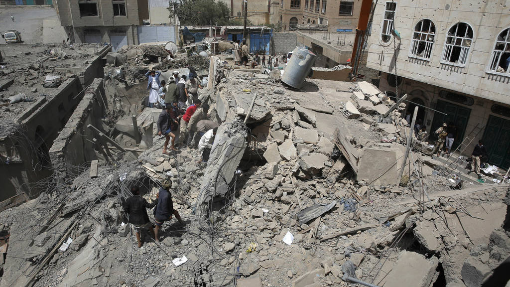 People search for survivors amid the rubble of houses destroyed in a