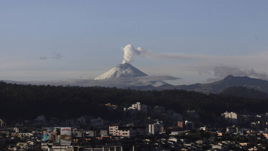 A plume of vapor rises from the Cotopaxi volcano as seen from Quito