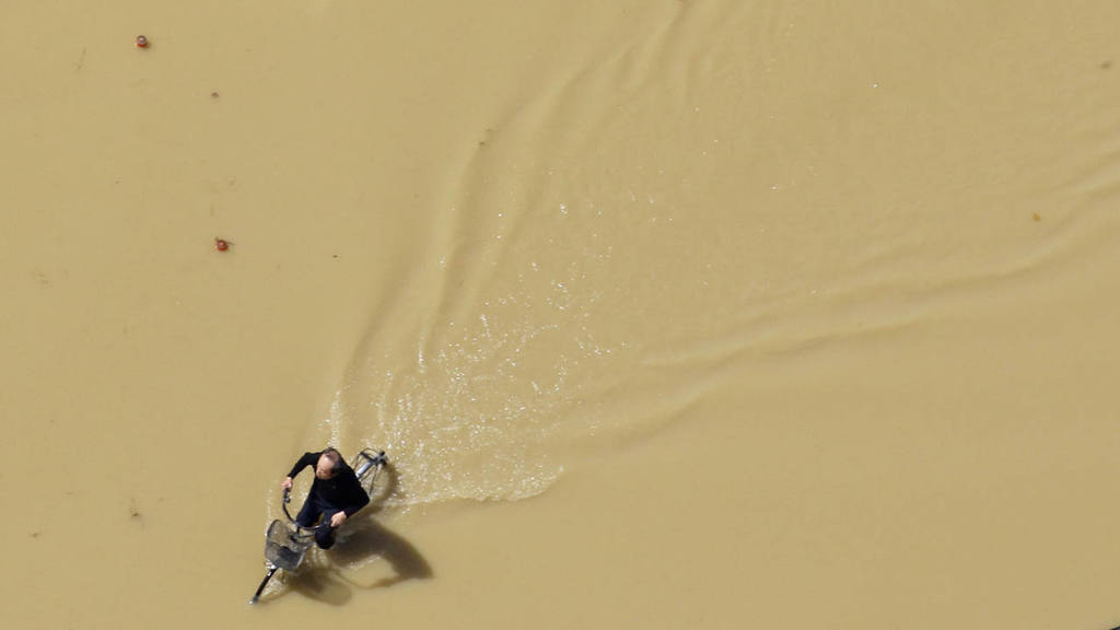 AP10ThingsToSee - A man rides a bicycle on a flooded road in Joso