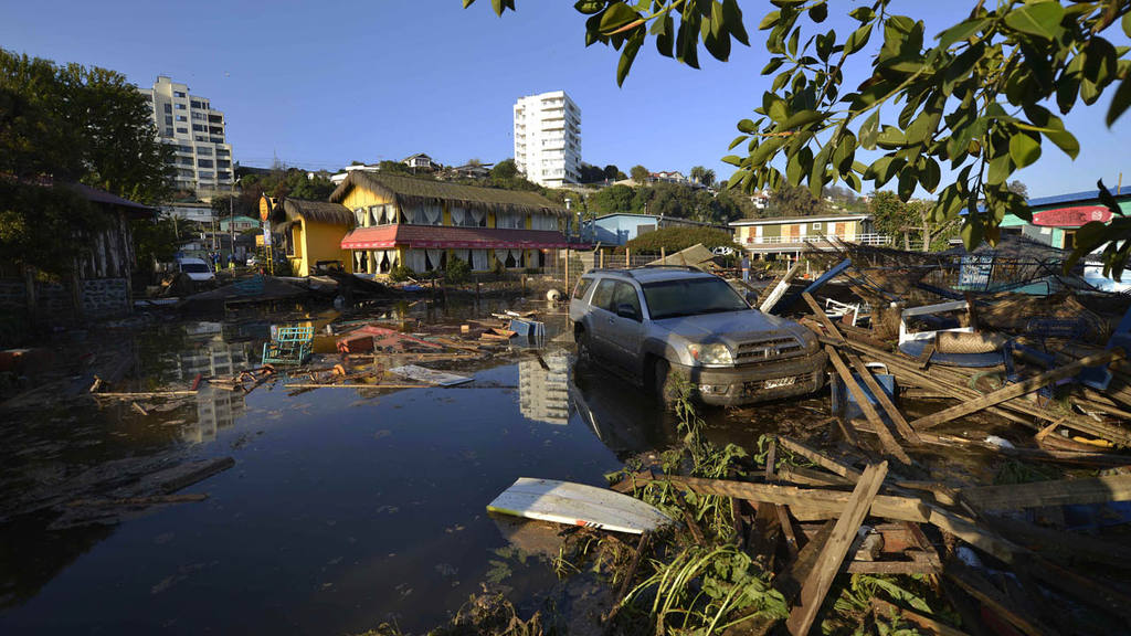 A car is surrounded by debris in a flooded street after an earthquake
