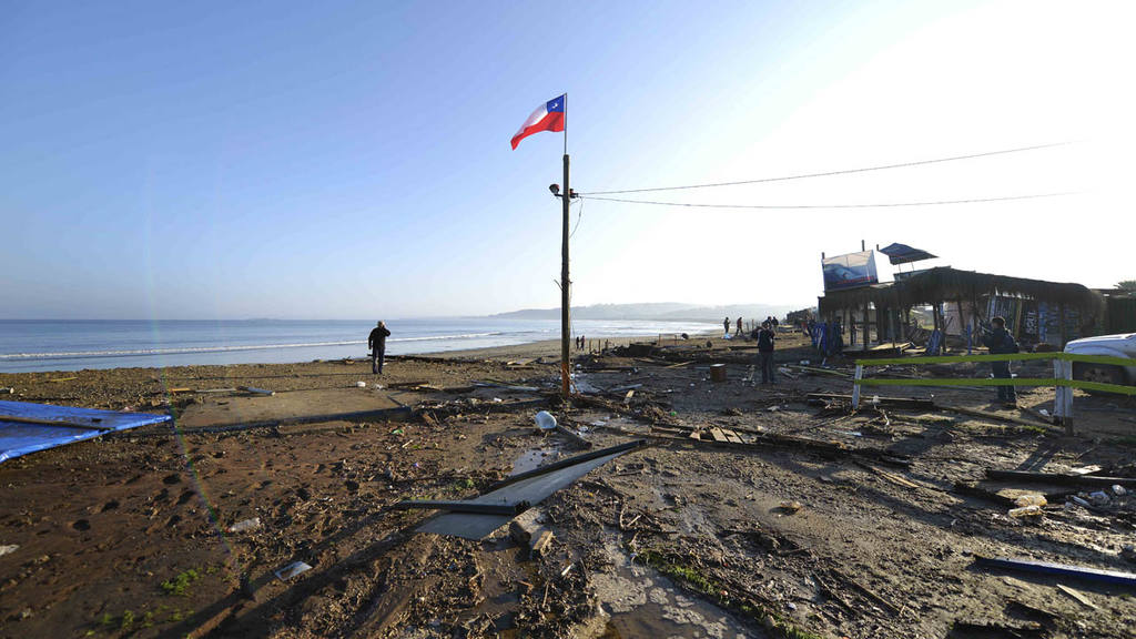 A man walks past a lone Chilean flag where surfing schools once stood