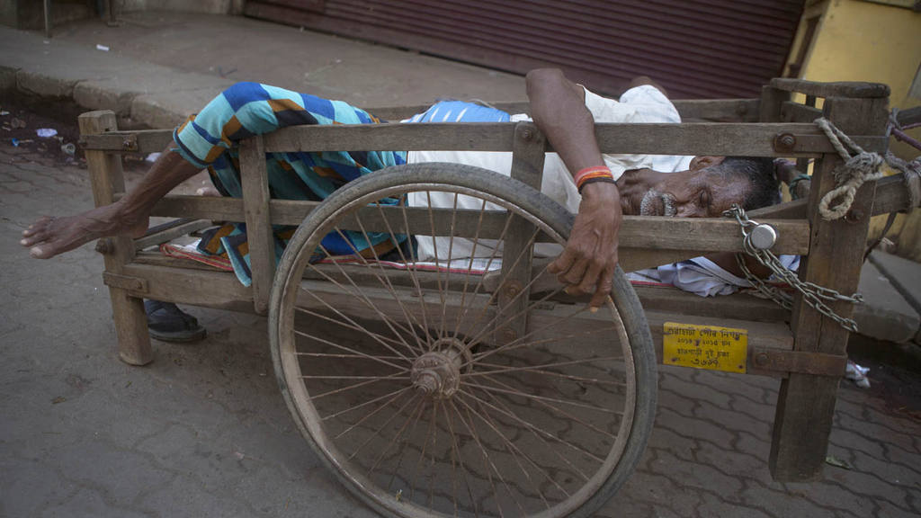 An Indian laborer sleeps on a push cart at a closed market during a 1
