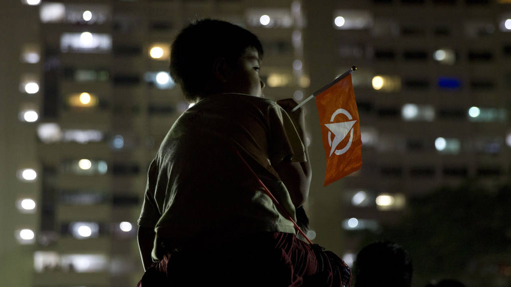 A child holds the flag for the opposition Singapore Democratic Party