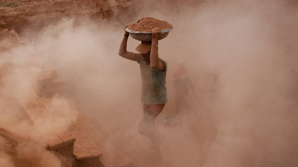 Indian laborers work at a brick kiln in Budgham area