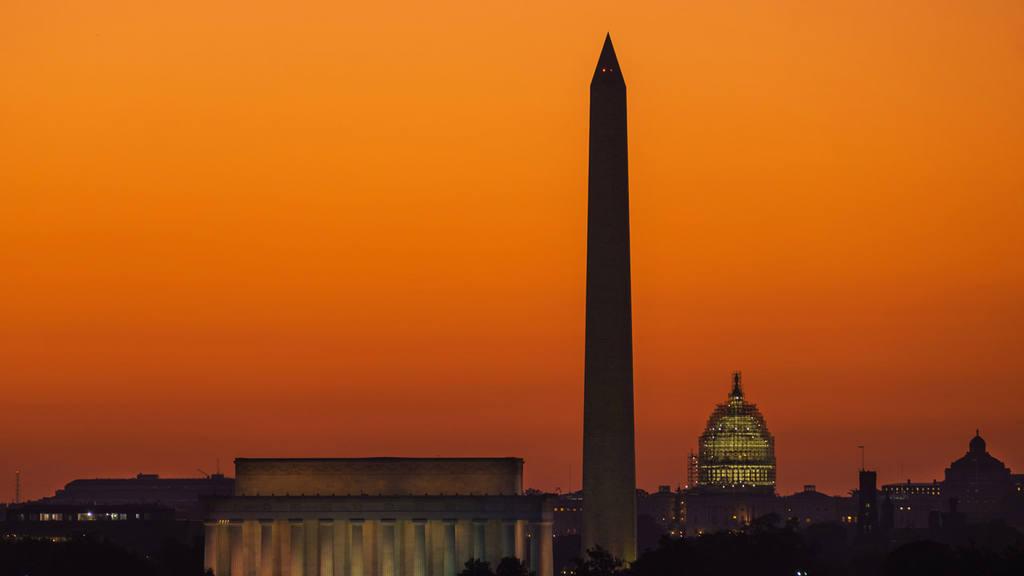 The orange sky of sunrise is captured behind the skyline of Washingto