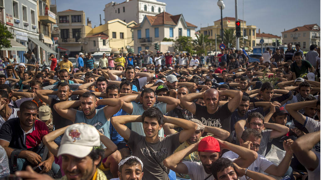 Refugees and migrants take part in a protest to demand faster process