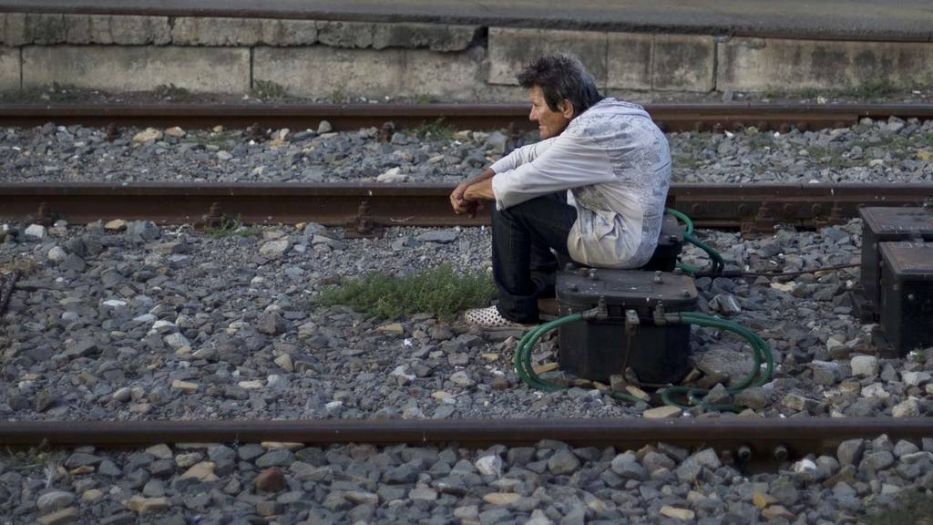 A homeless person sits between railway tracks at the main railway sta