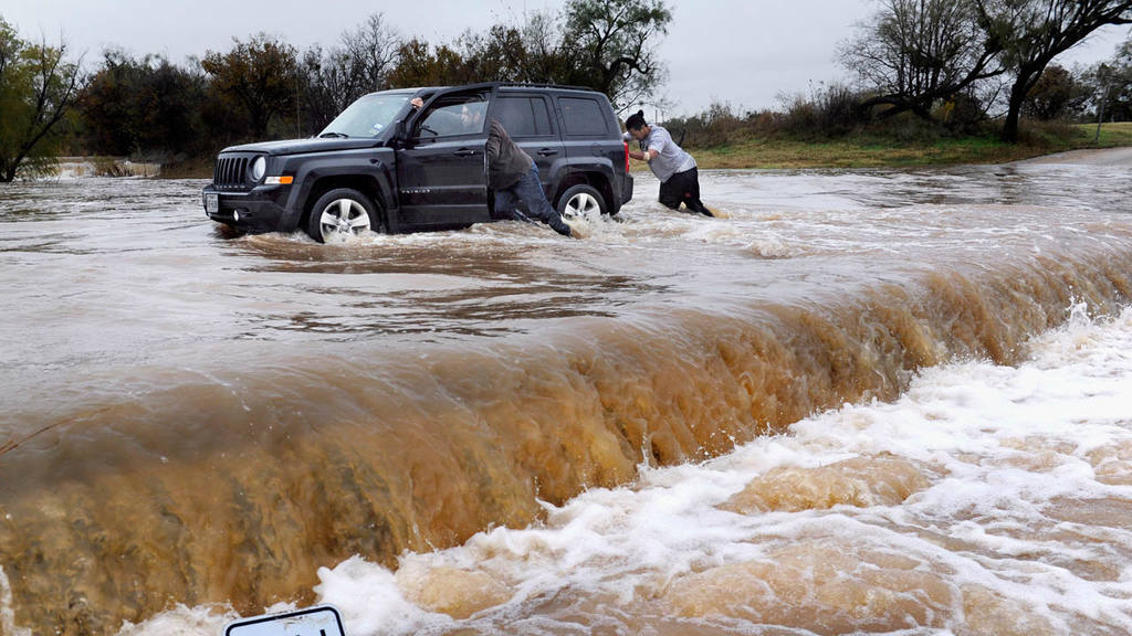 Two people push a vehicle out of high water at Cal Young Park