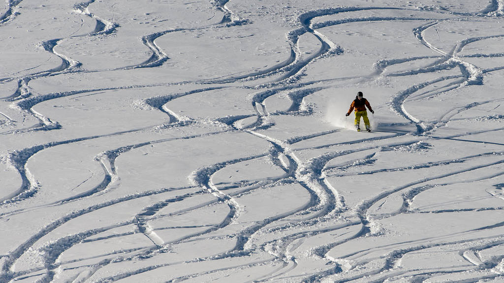 A person skis in powder snow on