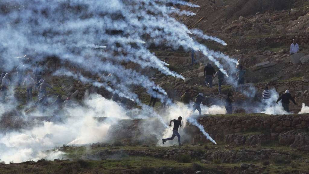 Palestinian protesters run from tear gas fired by Israeli troops duri