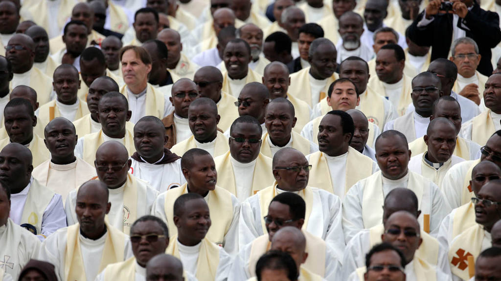 Priests attend a Mass celebrated by Pope Francis on the campus of the