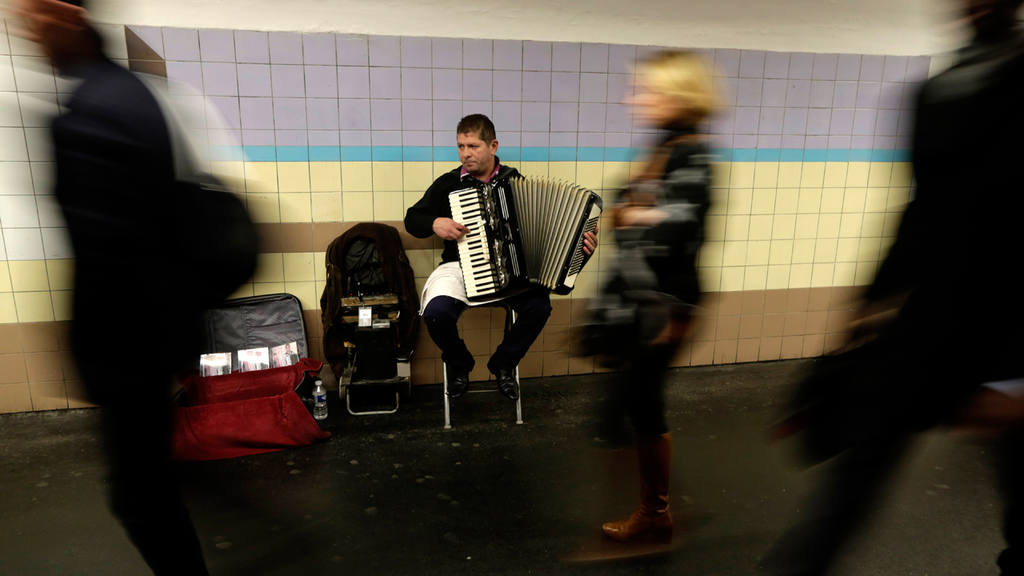 Commuters walks past an accordionist  in the Paris subway