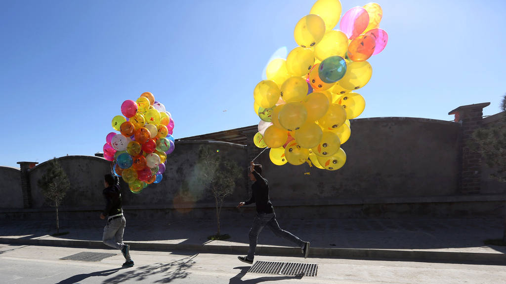 Afghan boys run as they hopes to sell colored balloons on a street in