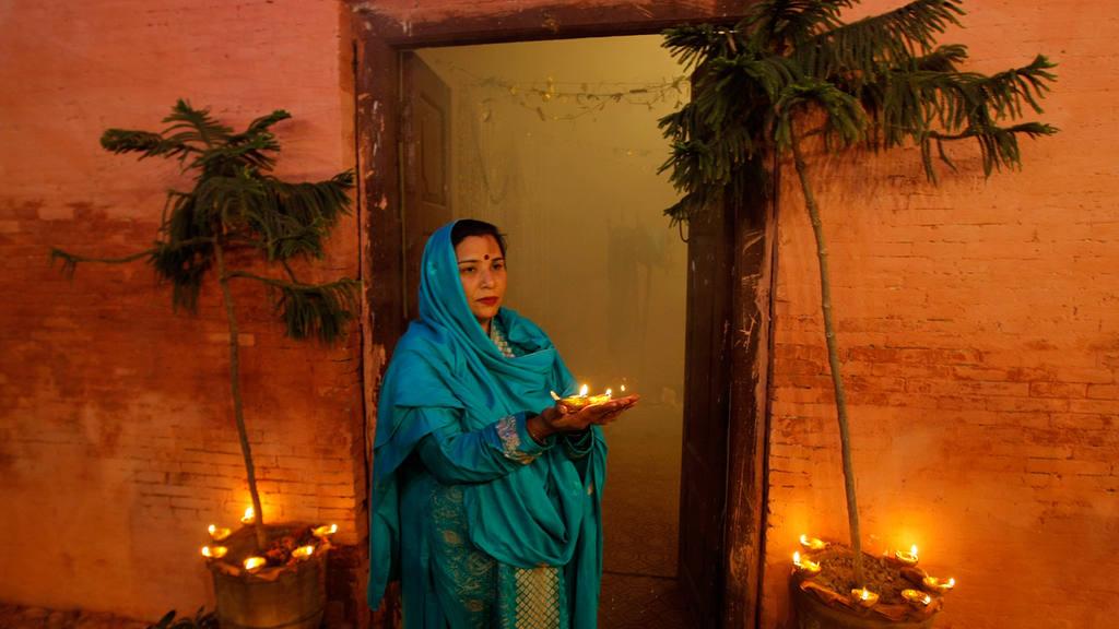 A Pakistani Hindu woman holds earthen lamps during Diwali celebration