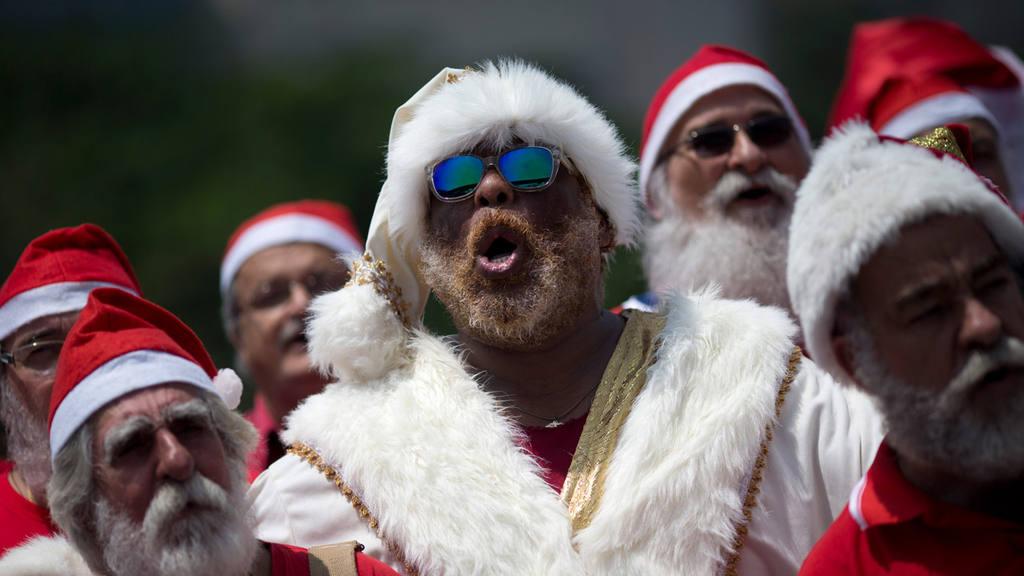 Recent graduates of a Santa school sing Christmas carols during their