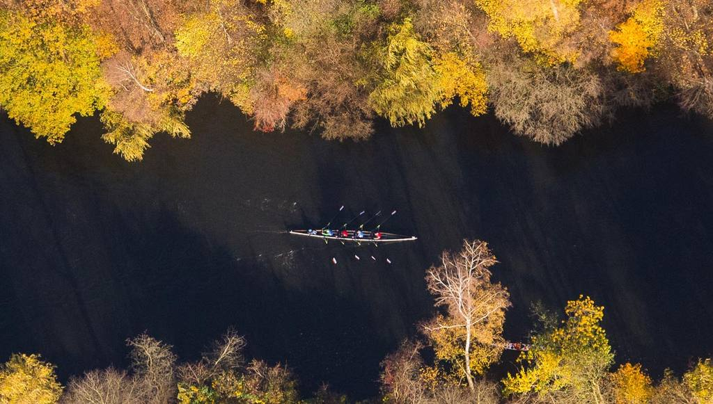 In this aerial view an eight rowing  boat   is framed by autumnal col