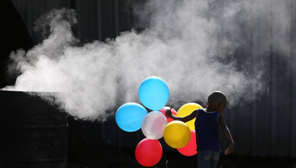A Filipino boy plays with balloons beside a burning trash in Manila