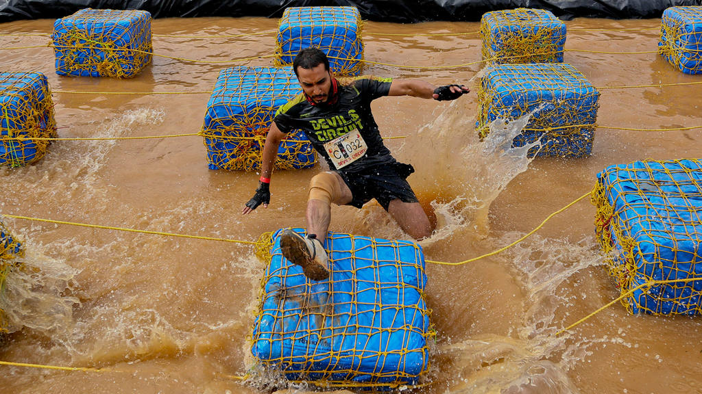 A participant loses his balance while attempting to cross an obstacle