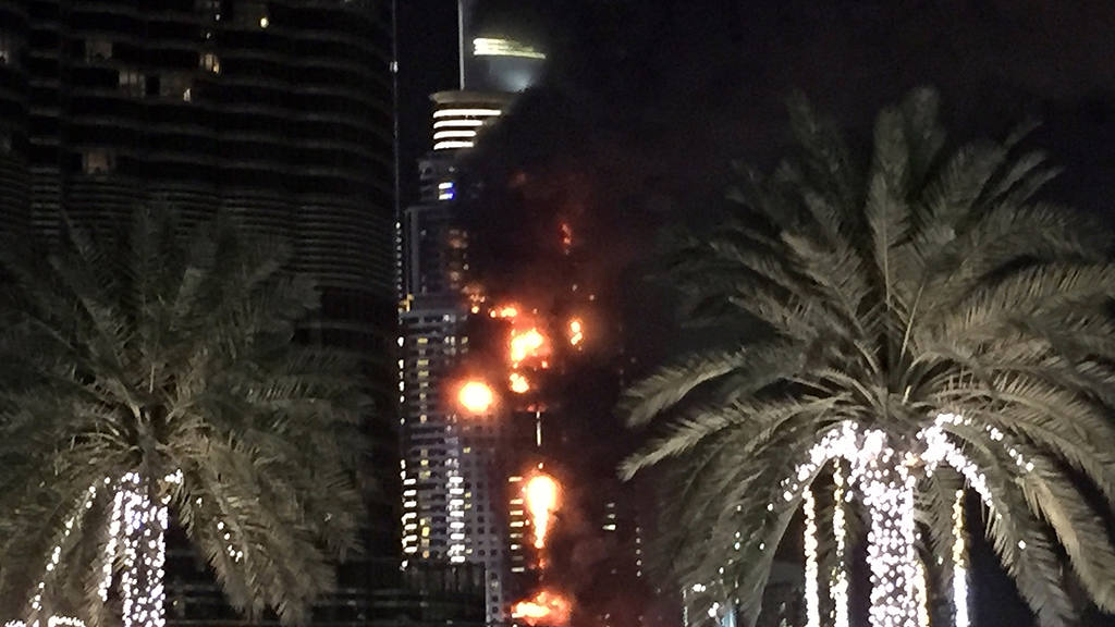 A fire runs up some 20 stories of a building in Dubai